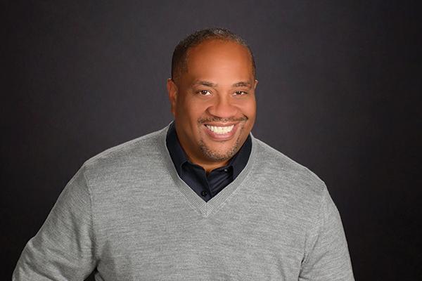 Business Headshot Photography - Man in gray sweater on dark gray background